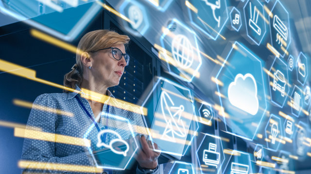 Female IT Server Specialist Standing in Data Center. View from Rack Server Cabinet with Cloud Server User Interface Icons and Visualization in the Foreground.