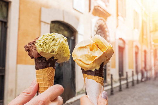 Two hands close-up holding cones with italian ice-cream gelato on the background of Rome streeet