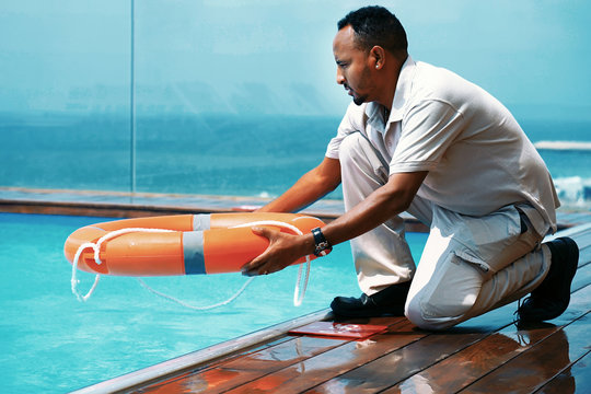 African man rescuer with lifebuoy in pool. African hotel worker throws a lifeline to man drowning pool. Salvation of a sinking person. Life ring in swimming pool. Red lifebuoy pool ring. Toning.