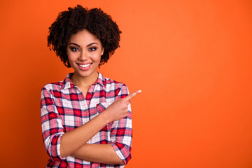 Close-up portrait of her she nice attractive cheerful cheery confident wavy-haired lady wearing checked shirt pointing aside tips feedback advert isolated on bright vivid shine orange background