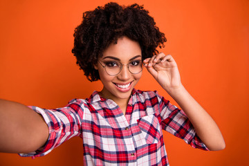 Photo of funny lady making selfies playful hold hand eyewear wear specs casual checkered shirt isolated orange bright background