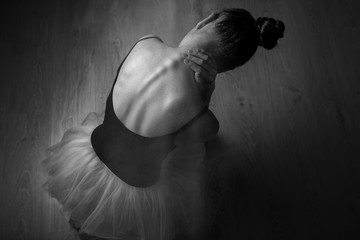 Tight back exhausting workouts and pain. Ballet dancer sits on the floor in dark lighted room stretches neck. Top view photo. Horizontal. Copy space