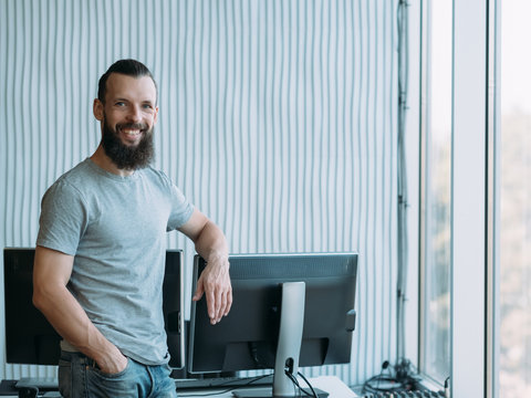 Successful professional career. Cheerful male network engineer standing at his workplace, smiling. Copy space.