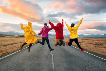 four friend jump on the road at sunset Wall mural