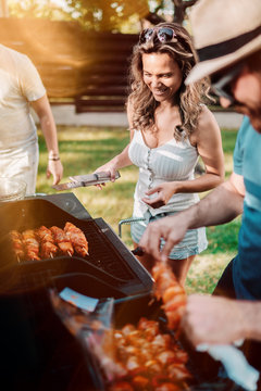 Happy woman cooking on barbecue grill with friends