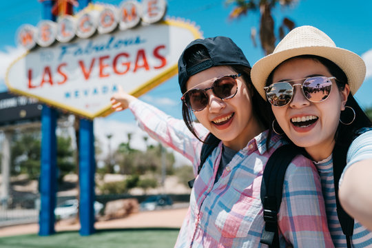 Close up lifestyle portrait of girls best friends make self picture and laughing together. Two japanese women traveler take selfie and showing blurred las vegas sign on back in sunny day in summer