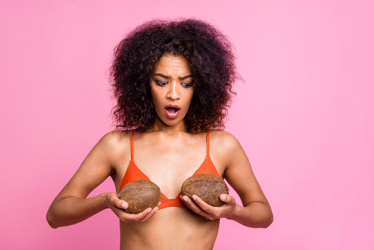 Close up photo beautiful she her dark skin bright lady hands arms hold coconuts try on new breast size chest speechless little cleavage brassiere wear swimming orange suit isolated pink background
