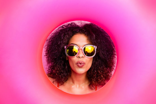 Close up photo beautiful she her dark skin lady enjoy seaside look through circle round rubber ring lifebuoy buoy send air kiss coquettish wear sun specs swimming orange suit isolated pink background