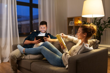 leisure and people concept - happy couple with tablet computer and book at home in evening
