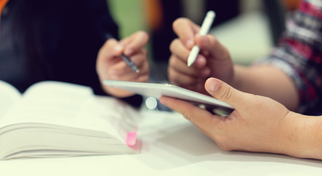 close up student man hand holding tablet and using stylus pen for asking or consulting about project with professor opening book for help to recommend or suggest at table , educational concept