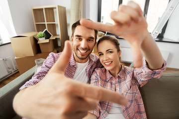 moving, repair and real estate concept - smiling couple taking selfie and making hand frame gesture...