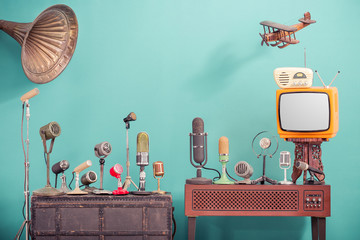 Retro old microphones for press conference or interview, outdated TV, radio, flying wooden toy plane and gramophone horn front gradient aquamarine wall background. Vintage old style filtered photo