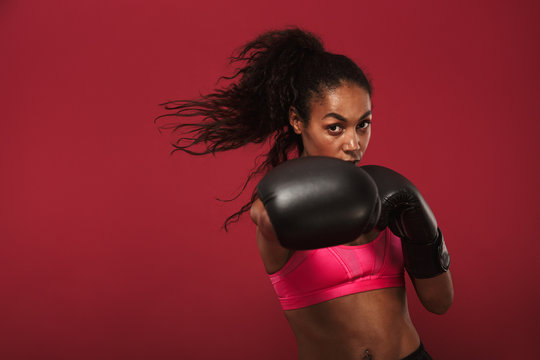 Serious strong young african sports woman boxer posing isolated over red wall background make boxing exercises.