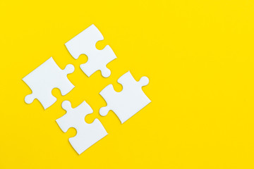 4 jigsaw puzzle on solid yellow background using as four important thing combine or working together to success or solve problem