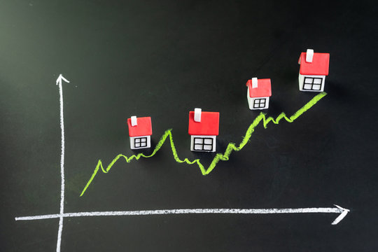 House, property or real estate market price go up or rising concept, small miniature house with green line graph going up on black chalkboard