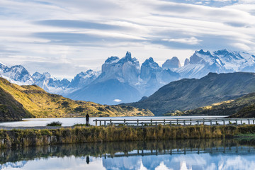 Beautiful panoramic view small people standing at the dock from the lake with Cuernos, horn mountains peak with lenticular cloud in autumn, Torres del Paine national park, south Patagonia, Chile Fototapete
