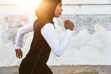 Strong muslim sports fitness woman dressed in hijab and dark clothes running outdoors.