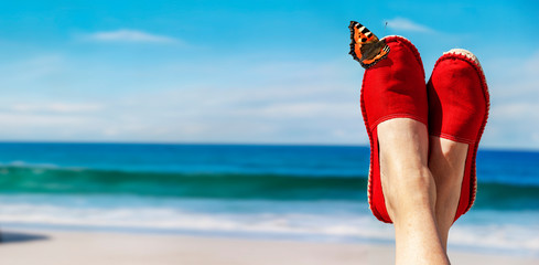 Beine mit roten Stoffschuhen vor Strand und Meer Fototapete