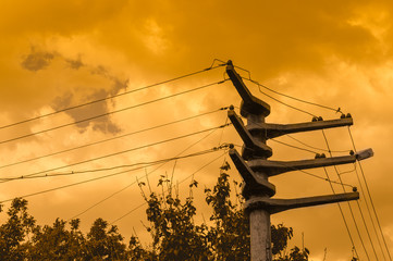 Wires attached to the electric mast at sunset