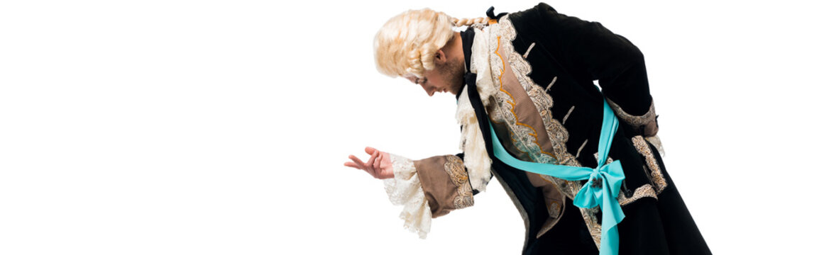 panoramic shot of handsome victorian gentleman in wig gesturing while bowing down isolated on white