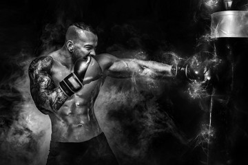 Sportsman man boxer fighting in gloves with boxing punching bag on dark background with smoke. Copy...