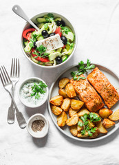 Mediterranean lunch table - baked lemon salmon with potatoes, greek salad, tzadziki sauce on light background, top view. Flat lay