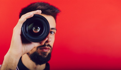 a brunette man looks through a camera line through a lens. a red background and a bearded and brunette boy. PLace the text.