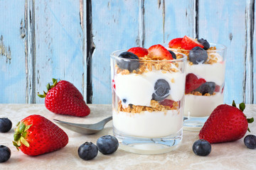 Strawberry and blueberry parfaits in glasses against a rustic blue wood background