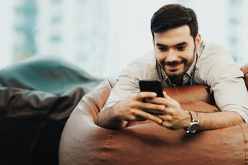 Smiling businessman using and relax smartphone device while sitting on sofa at home.  Man cheerful hipster guy typing an sms message at social network.  Technology Concept.