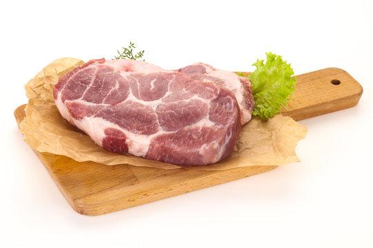 Raw pork steak over wooden board
