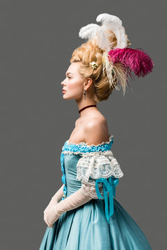 side view of elegant victorian woman in wig and blue dress isolated on grey