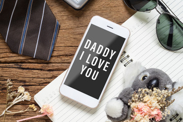 Father's day background concept. Mock up mobile phone for your artwork with Father's accessories items and daughter's toy on wood with Dady I love you messages on smartphone.
