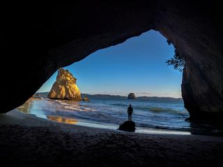 Un hombre mirando la playa, el horizonte y el mar desde una cueva