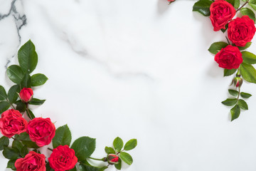 Flowers frame with roses buds and green leaves on marble background. Minimal flat lay style floral composition, top view, banner mock up. Valentine's day background.