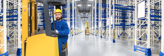 Huge distribution warehouse with high empty shelves and forklift with young driver.
