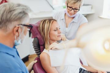 Zahnarzthelferin bereitet die Patientin auf die Untersuchung vor