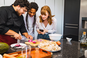 Professional cook teaching a black guy and a red Caucasian girl how to cook. She carries her mobile in her hand to make a video. Modern kitchen.