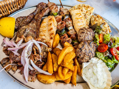 tasty dish with greek tzatziki sauce, a mixture of various types of grilled meat, chips and salad with onion and lemon for a meal