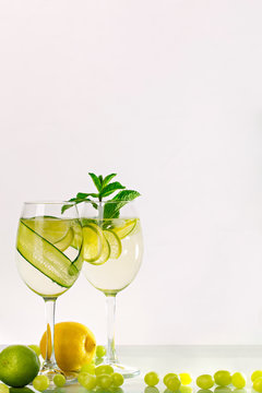 Two glasses of spritzer or lemonade with lime, cucumber, lemon and mint.
