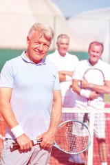 Portrait of confident mature man holding tennis racket while standing against friends on court during sunny day