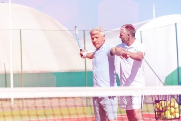 Mature man instructing friend swinging tennis racket on sunny day