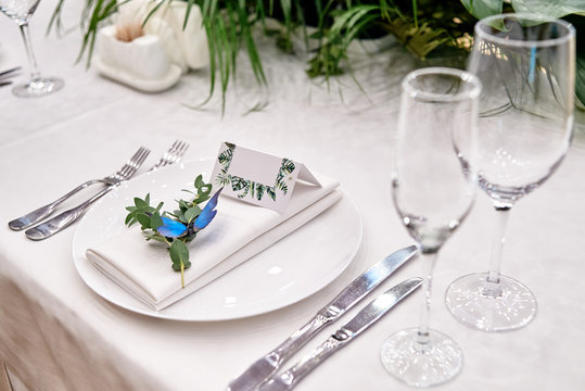 Table setting with blank guest card on empty white plate and cutlery on table, copy space. Menu mockup, place setting at wedding reception. Table served for wedding banquet in restauran