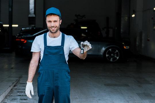 handsome bearded car mechanic holding keys in car service