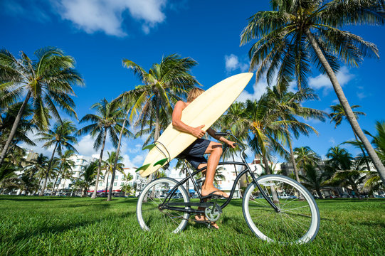 Surfer with blond hair carrying his surfboard on a beach cruiser bike through a tropical palm tree landscape in Miami, Florida, USA