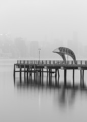 Black and White photo of a Pier at Williamsburg with Midtown Manhattan covered in fog on background