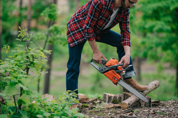 partial view of lumberjack in plaid shirt and denim jeans cutting wood with chainsaw in forest