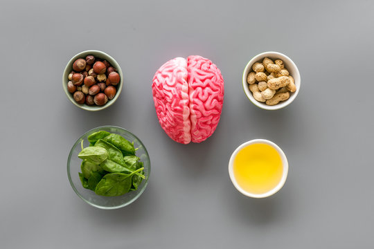 Brain food concept with peanut, hazelnut, seed-oil, spinage on gray background top view