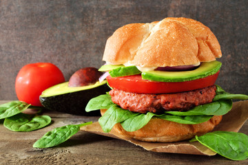 Plant based meatless burger with avocado, tomato and spinach against a dark background
