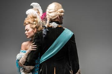 beautiful victorian woman hugging gentleman in wig on grey