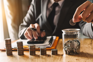 businessman holding coins putting in glass with using smartphone and calculator to calculate  concept saving money for finance accounting